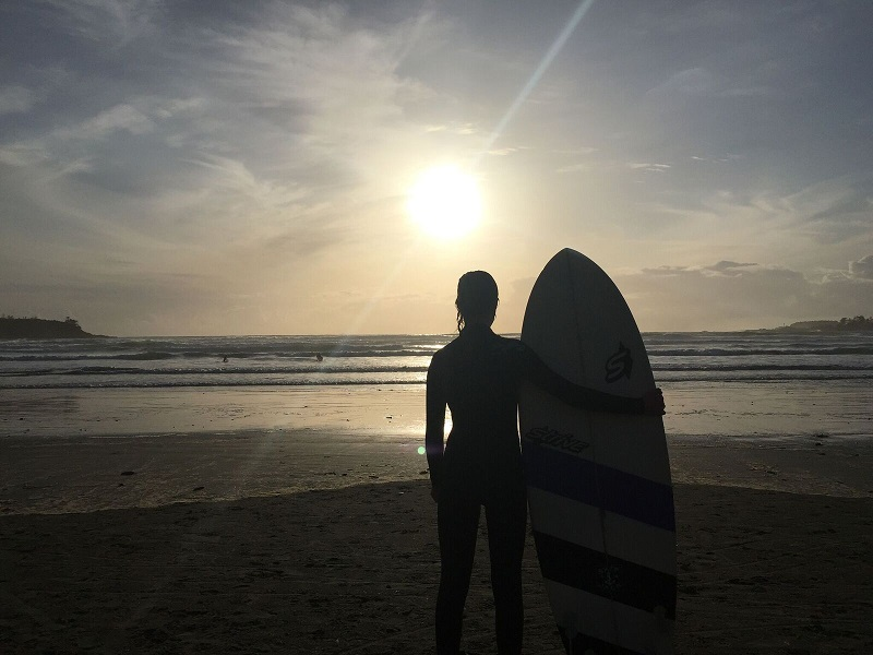 Surfer with surf board in sunset