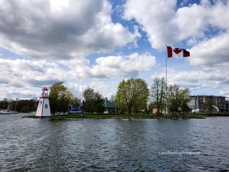View of lighthouse and Canadian flag leaving Gananoque harbour by boat